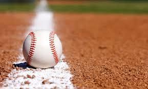 A baseball on the ground of a baseball field.